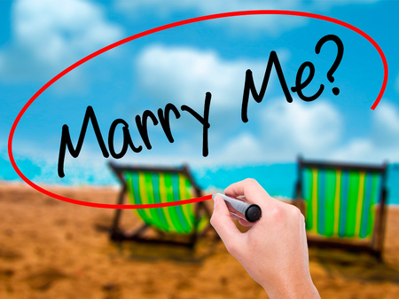 Man Hand writing Marry Me? with black marker on visual screen. Isolated on sunbed on the beach. Business, technology, internet concept. Stock  Photo