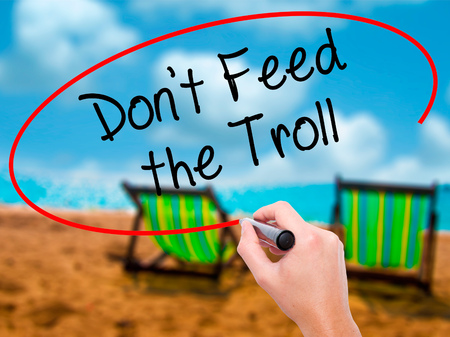 sarcastic: Man Hand writing Dont Feed the Troll with black marker on visual screen. Isolated on sunbed on the beach. Business, technology, internet concept. Stock Photo