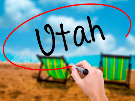 Man Hand writing Utah with black marker on visual screen. Isolated on sunbed on the beach. Business, technology, internet concept. Stock Photo