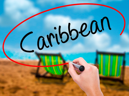Man Hand writing Caribbean with black marker on visual screen. Isolated on sunbed on the beach. Business, technology, internet concept. Stock Photo Stock Photo