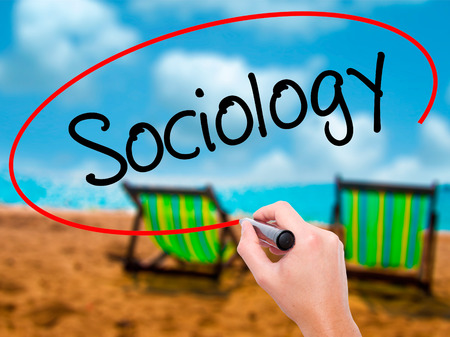 sociologia: Man Hand writing Sociology  with black marker on visual screen. Isolated on sunbed on the beach. Business, technology, internet concept. Stock Photo