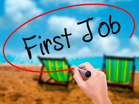 Man Hand writing First Job with black marker on visual screen. Isolated on sunbed on the beach. Business, technology, internet concept. Stock Photo