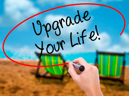 enrich: Man Hand writing Upgrade Your Life!  with black marker on visual screen. Isolated on sunbed on the beach. Business, technology, internet concept. Stock Photo Stock Photo