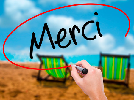 comunicación escrita: Man Hand writing Merci  (Thank You In French) with black marker on visual screen. Isolated on sunbed on the beach. Business, technology, internet concept. Stock Photo