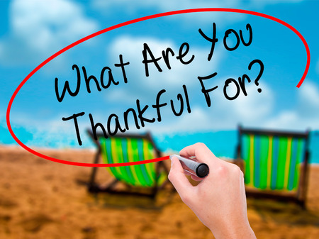 Man Hand writing What Are You Thankful For? with black marker on visual screen. Isolated on sunbed on the beach. Business, technology, internet concept.