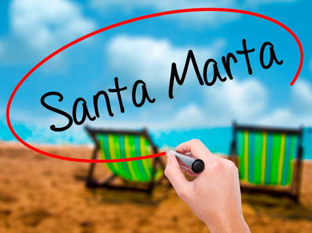 marta: Man Hand writing Santa Marta with black marker on visual screen. Isolated on sunbed on the beach. Business, technology, internet concept. Stock Photo
