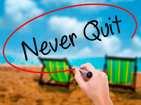 Man Hand writing Never Quit with black marker on visual screen. Isolated on sunbed on the beach. Business, technology, internet concept. Stock  Photo