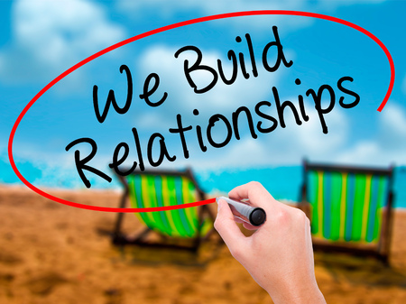 Man Hand writing We Build Relationships with black marker on visual screen. Isolated on sunbed on the beach. Business, technology, internet concept. Stock Photo