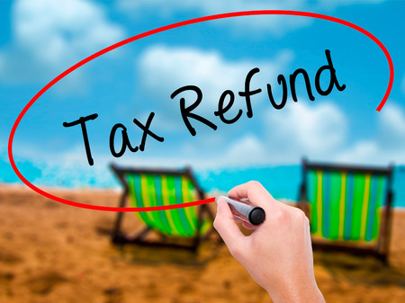 Man Hand writing Tax Refund with black marker on visual screen. Isolated on sunbed on the beach. Business, technology, internet concept. Stock Photo