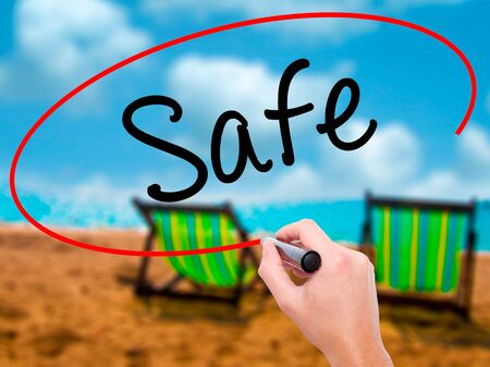 peril: Man Hand writing Safe with black marker on visual screen. Isolated on sunbed on the beach. Business, technology, internet concept. Stock Image