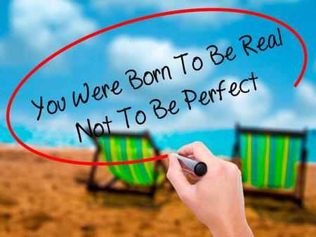 true born: Man Hand writing You Were Born To Be Real Not To Be Perfect with black marker on visual screen. Isolated on sunbed on the beach. Business, technology, internet concept.