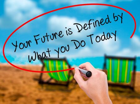 Man Hand writing Your Future is Defined by What you Do Today  with black marker on visual screen. Isolated on sunbed on the beach. Business, technology, internet concept. Stock Photo