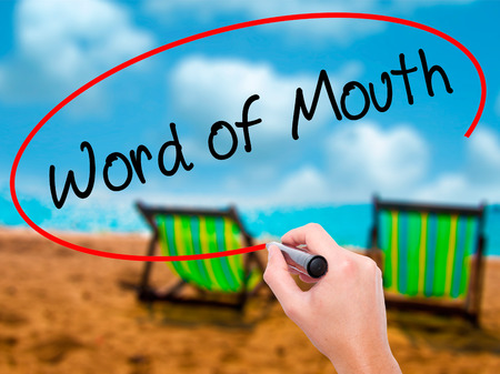 referrer: Man Hand writing Word of Mouth  with black marker on visual screen. Isolated on sunbed on the beach. Business, technology, internet concept. Stock Photo