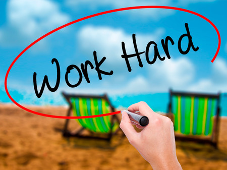 ambitious: Man Hand writing Work Hard with black marker on visual screen. Isolated on sunbed on the beach. Business, technology, internet concept. Stock Photo Stock Photo