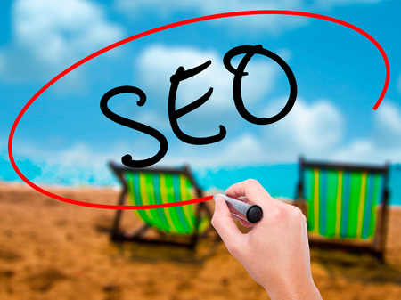 Man Hand writing SEO with marker on transparent wipe board. Isolated on sunbed on the beach. Business, internet, technology concept. Stock Photo
