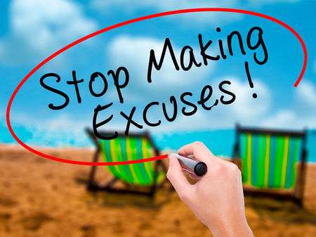 Man Hand writing Stop Making Excuses with black marker on visual screen. Isolated on sunbed on the beach. Business, technology, internet concept. Stock Image Stock Photo