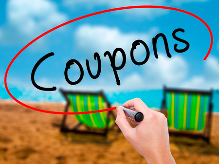 Man Hand writing Coupons black marker on visual screen. Isolated on sunbed on the beach. Business, technology, internet concept. Stock Image Stock Photo