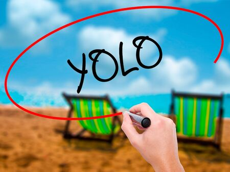 Man Hand writing YOLO (You Only Live Once) with black marker on visual screen. Isolated on sunbed on the beach. Business, technology, internet concept. Stock Photo