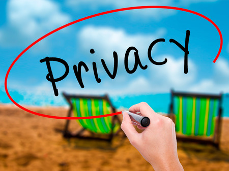 Man Hand writing Privacy with black marker on visual screen. Isolated on sunbed on the beach. Business, technology, internet concept. Stock Image