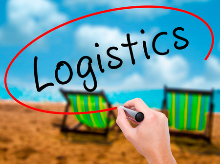 Man Hand writing Logistics with black marker on visual screen. Isolated on sunbed on the beach. Business, technology, internet concept. Stock Image