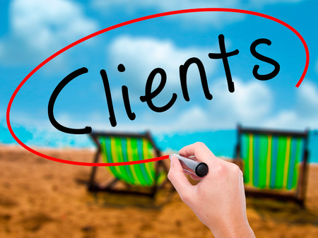 Man Hand writing Clients with black marker on visual screen. Isolated on sunbed on the beach. Business, technology, internet concept. Stock Image