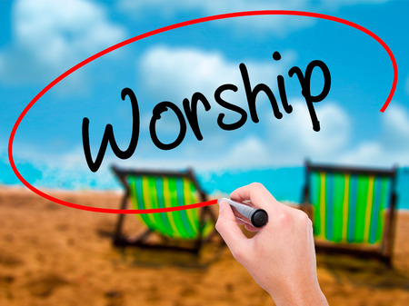 Man Hand writing Worship with black marker on visual screen. Isolated on sunbed on the beach. Business, technology, internet concept. Stock Photo
