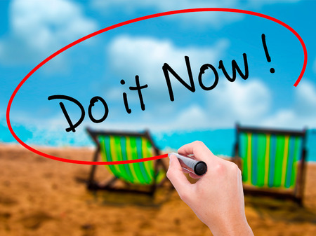 Man Hand writing Do it Now with black marker on visual screen. Isolated on sunbed on the beach. Business, technology, internet concept. Stock Image