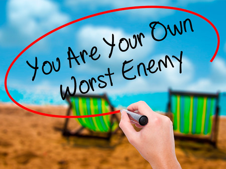enemy: Man Hand writing You Are Your Own Worst Enemy with black marker on visual screen. Isolated on sunbed on the beach. Business, technology, internet concept. Stock Photo