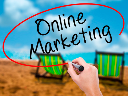 Man Hand writing Online Marketing with black marker on visual screen. Isolated on sunbed on the beach. Business, technology, internet concept. Stock Image Stock Photo