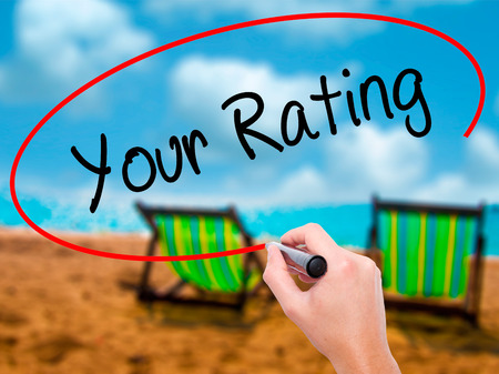 Man Hand writing Your Rating with black marker on visual screen. Isolated on sunbed on the beach. Business, technology, internet concept. Stock Photo