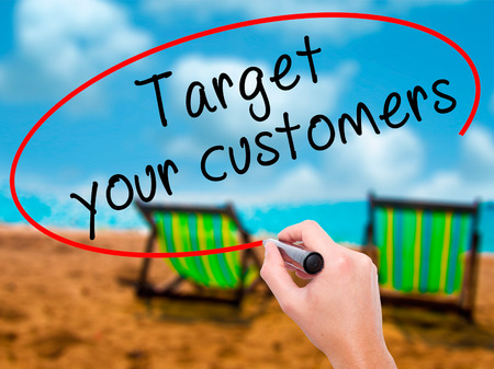 Man Hand writing Target your customers with black marker on visual screen. Isolated on sunbed on the beach. Business, technology, internet concept. Stock Image Stock Photo