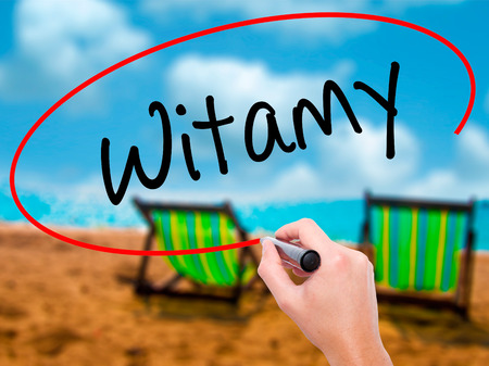 Man Hand writing Witamy (Welcome in Polish) with black marker on visual screen. Isolated on sunbed on the beach. Business, technology, internet concept. Stock Photo