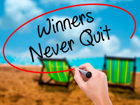 Man Hand writing Winners Never Quit with black marker on visual screen. Isolated on sunbed on the beach. Business, technology, internet concept. Stock Photo Stock Photo