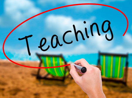Man Hand writing Teaching with black marker on visual screen. Isolated on sunbed on the beach. Business, technology, internet concept. Stock Image