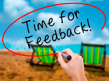 Man Hand writing Time for Feedback with black marker on visual screen. Isolated on sunbed on the beach. Business, technology, internet concept. Stock Image