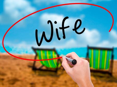 ex wife: Man Hand writing Wife with black marker on visual screen. Isolated on sunbed on the beach. Business, technology, internet concept. Stock Photo