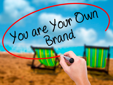 Man Hand writing You are Your Own Brand with black marker on visual screen. Isolated on sunbed on the beach. Business, technology, internet concept. Stock Photo
