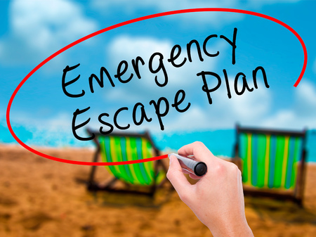emergency plan: Man Hand writing Emergency Escape Plan with black marker on visual screen. Isolated on sunbed on the beach. Business, technology, internet concept. Stock Image