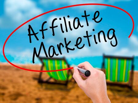 affiliation: Man Hand writing Affiliate Marketing with black marker on visual screen. Isolated on sunbed on the beach. Business, technology, internet concept. Stock Image Stock Photo