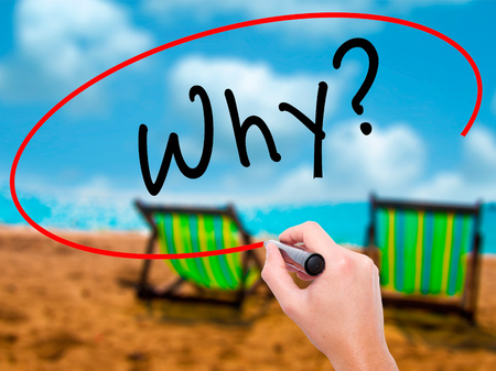 Man Hand writing Why? with black marker on visual screen. Isolated on sunbed on the beach. Business, technology, internet concept. Stock Photo
