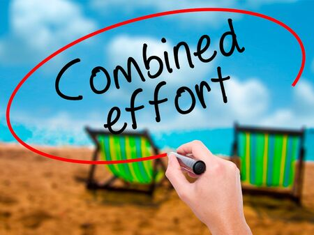 combined effort: Man Hand writing Combined effort with black marker on visual screen. Isolated on sunbed on the beach. Business, technology, internet concept. Stock Image