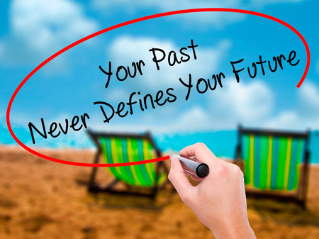 defines: Man Hand writing Your Past Never Defines Your Future with black marker on visual screen. Isolated on sunbed on the beach. Business, technology, internet concept. Stock Photo