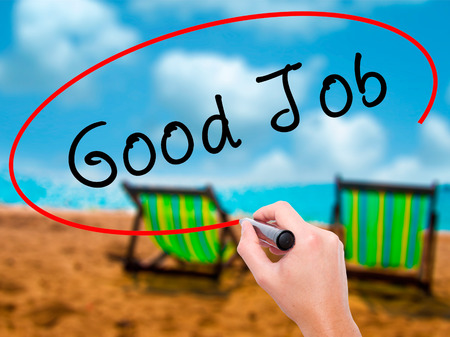 Man Hand writing Good Job with marker on transparent wipe board. Isolated on sunbed on the beach. Business, internet, technology concept. Stock Photo
