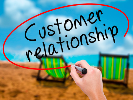 Man Hand writing Customer relationship with black marker on visual screen. Isolated on sunbed on the beach. Business, technology, internet concept. Stock Image