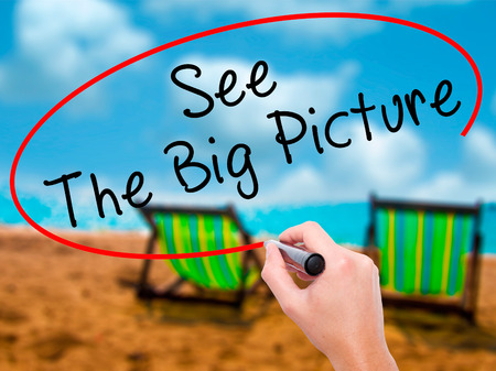 big picture: Man Hand writing See The Big Picture with black marker on visual screen. Isolated on sunbed on the beach. Business, technology, internet concept. Stock Image