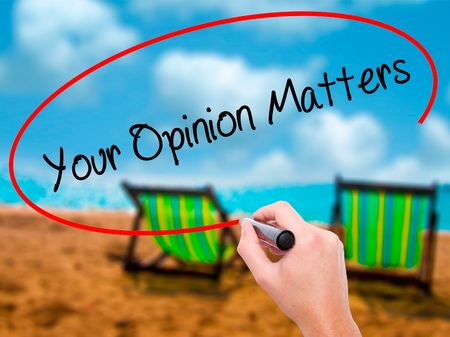 Man Hand writing Your Opinion Matters with black marker on visual screen. Isolated on sunbed on the beach. Business, technology, internet concept.