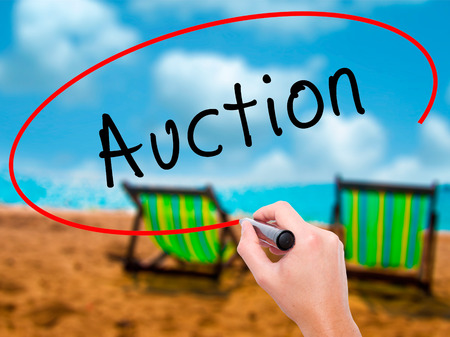 Man Hand writing Auction with black marker on visual screen. Isolated on sunbed on the beach. Business, technology, internet concept. Stock Image