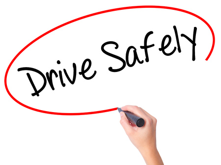 drive safely: Women Hand writing  Drive Safely with black marker on visual screen. Isolated on white. Business, technology, internet concept. Stock Photo