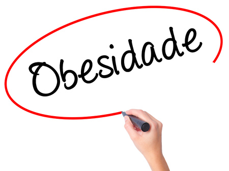 Women Hand writing Obesidade (Obesity in Portuguese)  with black marker on visual screen. Isolated on white. Business, technology, internet concept. Stock Photo