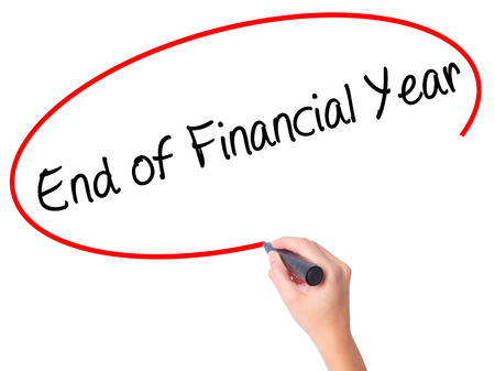 Women Hand writing End of Financial Year with black marker on visual screen. Isolated on white. Business, technology, internet concept. Stock Photo Stock Photo